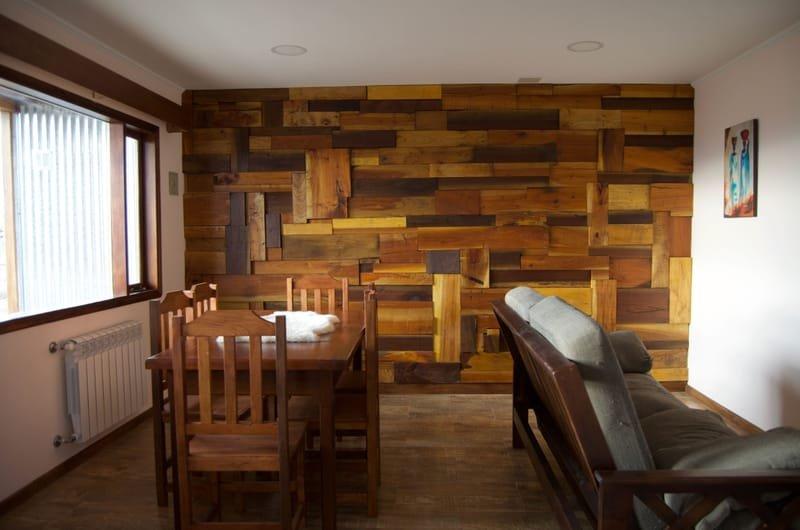 Amplia sala de estar con sofa cama, televisor pantalla plana, mesa y sillas. de cedro. Detalles  realizados con mas maderas mas sofisticadas brindando un ambiente cálido y familiar